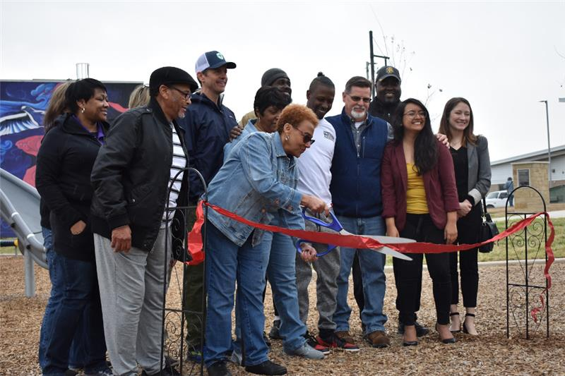 Barbara Scott and other community members gather at a ribbon-cutting ceremony to celebrate the grand opening of Colony Park District Park.