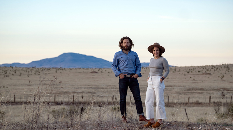 Maisie Crow and husband Max Kabat standing outside in West Texas, where they own a newspaper.