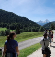 students walking along a path with mountain scenery in the background